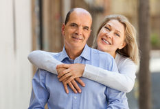 MAture woman hugging man while walking Royalty Free Stock Photo