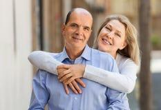 MAture woman hugging man while walking Royalty Free Stock Photo