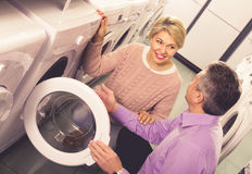 Mature woman with husband selecting washing machine. Mature women with husband selecting modern washing machine in appliances shop Stock Photo
