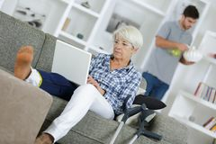Mature woman with injured leg relaxing on sofa Stock Photos