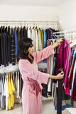 Mature woman inspecting her Clothing Royalty Free Stock Images
