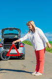 Mature woman is installed warning triangle on the road Royalty Free Stock Images