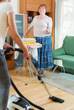 Mature woman with iron do housework. Mature women with iron do housework and her daughter help cleaning home Royalty Free Stock Photo