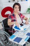 Mature woman ironing at home while sitting on wheelchair royalty free stock photos