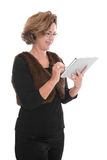 Mature woman isolated on white holding her tablet pc. Stock Photos