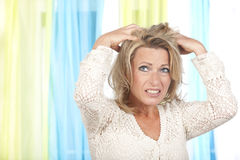 Mature woman with itchy scalp. Mature woman with itchy and dry scalp royalty free stock photo