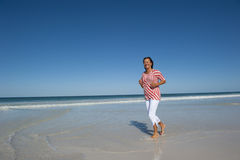 Mature Woman Jogging at Beach Stock Photography