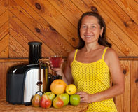 Mature woman with juicer machine Royalty Free Stock Photos