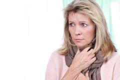 Mature woman with sore throat and scarf. Mature woman keeping her throat warm with a scarf Royalty Free Stock Images