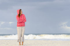 Mature woman keeping warm at beach Stock Image