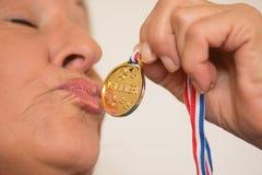 Mature woman kissing medal award Stock Photo