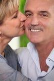 Mature woman kissing a smiling man Stock Photos