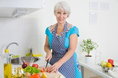 Mature woman on the kitchen Stock Images