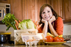 Mature woman in kitchen with fresh ingredients Royalty Free Stock Image