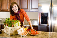 Mature woman in kitchen with fresh ingredients Royalty Free Stock Photos