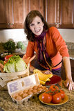 Mature woman in kitchen with fresh produce. Happy attractive middle-aged woman in kitchen with fresh produce on counter Royalty Free Stock Photography
