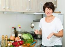 Mature woman kitchen soup Stock Image