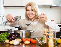 Mature woman with ladle cooking soup in pan at  kitchen Stock Photos