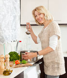 Mature  woman  with ladle cooking soup in pan  in kitchen  interior Royalty Free Stock Image