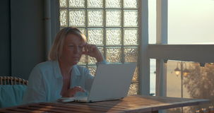 Mature Woman with Laptop on the Balcony stock video