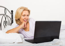 Mature woman with laptop in bed Royalty Free Stock Images