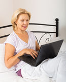 Mature woman with laptop in bed Stock Photo