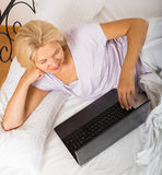 Mature woman with laptop in bed Stock Images