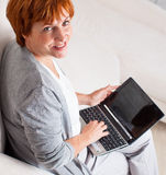 Mature woman with laptop at home Stock Image