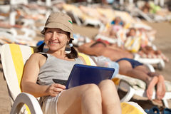 Mature woman  with laptop at resort Royalty Free Stock Photos