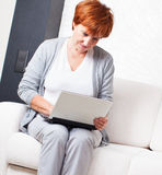Mature woman with laptop at sofa Royalty Free Stock Images