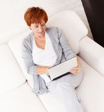 Mature woman with laptop at sofa Stock Photos