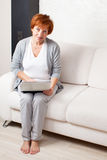 Mature woman with laptop at sofa Stock Photography