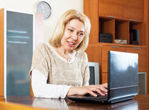 Mature woman  with laptop  at table Royalty Free Stock Photo