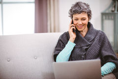 Mature woman with laptop talking on mobile phone at home Royalty Free Stock Photography