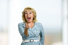 Mature woman laughing on blurred background. Adult lady laughing with wide open mouth and pointing on somebody index finger Stock Photos