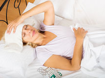 Mature woman laying in bed with towel. On forehead at bedroom stock photography