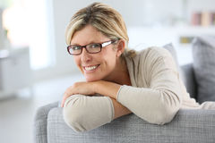 Mature woman leaning on sofa Stock Image
