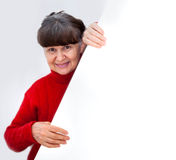 Mature woman leaning on white banner smiling against of white background Stock Photography