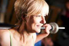Mature woman lifting barbell Royalty Free Stock Photo