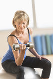 Mature Woman Lifting Dumbbell On Fitness Ball Royalty Free Stock Image