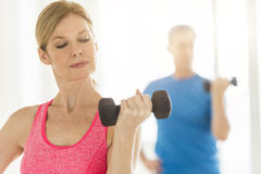Mature Woman Lifting Dumbbell With Man In Background At Home Royalty Free Stock Photos