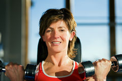 Mature woman lifting dumbbells Stock Photography