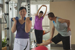 mature woman lifting weights in the foreground, people exercising in the background Stock Image