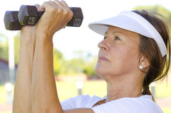Mature woman lifting weights I Stock Images