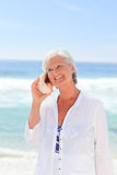 Mature woman listening to her shell Royalty Free Stock Photo