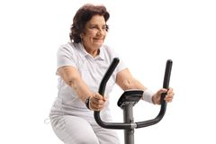 Mature woman listening to music and exercising on a stationary b. Ike isolated on white background Stock Images