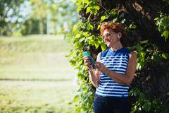Mature woman listening to the music in the park. Mature woman listening to the music on headphones in the park stock photography