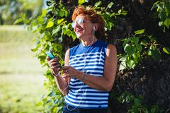 Mature woman listening to the music in the park. Mature woman listening to the music on headphones in the park stock photos