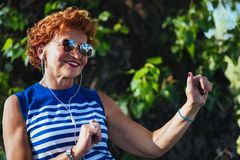 Mature woman listening to the music in the park. Mature woman listening to the music on headphones in the park royalty free stock image