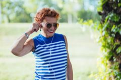 Mature woman listening to the music in the park. Mature woman listening to the music on headphones in the park stock images
